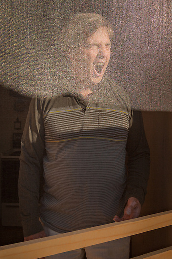 David Freeman greets the morning from behind the screen door of his cabin in the Kenai Keys subdivision on the Kenai River near Soldotna, Alaska. (© Clark James Mishler)