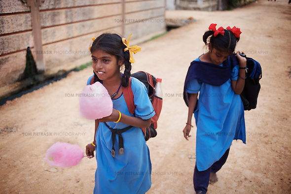 "Vijita (right) and Vijyashree Viswanathan head home to their fishing village after a day at the Government Girls High School, Venugopalapuram, Cuddalore...Vijita (age 14) and Vijyashree (age 11) Viswanathan lost their mother and brother to the tsunami in 2004. They continue to live in the fishing village of Thazanguda with their father Viswanathan, his second wife Kayalvizhi and their two children Sanjay (age 3) and Monica (age 1). ..Until the beginning of the 2009 academic year in June, Vijita and Vijyashree attended the local Thazanguda school. This village school teaches pupils only until the 8th Standard and with Vijita now entering the 9th, it was decided that the two daughters remain together and both travel 3km to the local town school: the Government Girls High School, Venugopalapuram in Cuddalore. ..At the same time Viswanathan decided he would cease day-to-day care of his daughters and place them in the Government Home for Tsunami Children, also in Cuddalore. This was not a move welcomed by either Vijita or Vijyashree and one afternoon after just two weeks at the orphanage, the two girls ran away. At roll call in the orphanage that evening the alarm was sounded and the two sisters were eventually located in Thazanguda waiting for their father and Kayalvizhi who were both away at the time. Realising his daughters' unhappiness, Viswanathan then took them out of the Government home. ..According to her class teacher, Vijita often compares her step-mother to her mother and concludes that she wants her mother back. Vijita confides in her teachers that her stepmother is forever demanding that she and her sister Vijyashree undertake housework. This frustration at home is tempered by the genuine love both sisters have for their father and two younger siblings Sanjay and Monica. Vijita expresses a lonelyness without her mother. Vijita's class teacher Pushpavalli concludes that ""Vijita wants something else beyond the love of her father and sister"". ..Viswanathan appe (Tom Pietrasik)"