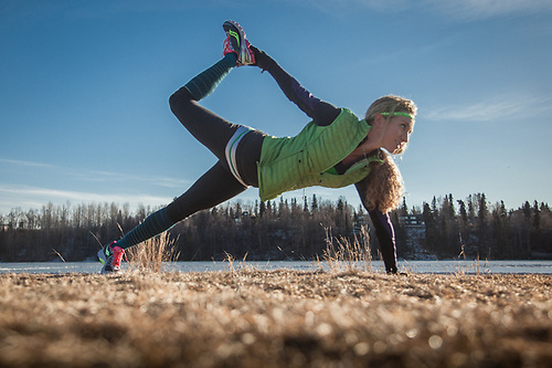 Desiree Bax performs the Partridge Pose before a run at Westchester Lagoon, Anchorage (© Clark James Mishler)
