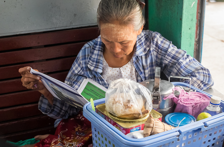 YANGON, MYANMAR - CIRCA DECEMBER 2013: Old Burmese woman reading a newspaper while awaits train to depart from Yangon Central Railway Station (Daniel Korzeniewski)