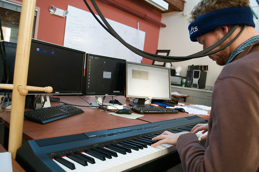 BACh mock experiment at Tufts HCI Lab. PhD student places electrodes on his head (holds them with band) in order to assess electrical impulses while playing simple assigned melodies on the keyboard. 3/8/16-Medford/Somerville, MA- BACh experiment @ Tufts HCI Lab. Professor Robert Jacob mentors PhD students in the pictures. on March 08th, 2016. (Maria Ferraz / The Tufts Daily) (Daily Photo)