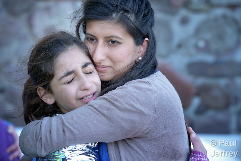Zoya Hameed (right), a physician from the United Kingdom, hugs Hanin, a frightened Syrian refugee girl, on a beach near Molyvos, on the Greek island of Lesbos, on October 30, 2015. The girl was on a boat full of refugees that traveled to Lesbos from Turkey. The boat was provided by Turkish traffickers to whom the refugees paid huge sums to arrive in Greece. Hameed is one of hundreds of volunteers on the island who receive the refugees and provide them with warm clothing and medical care before they continue their journey toward western Europe. (Paul Jeffrey)