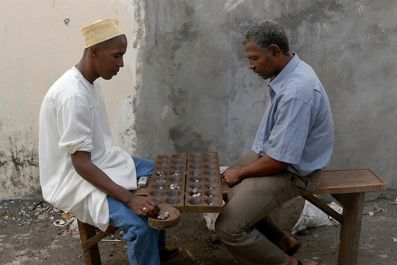 Two dark skinned men are playing a game. Comores. Grand Comore. Moroni. (Michael Runkel)