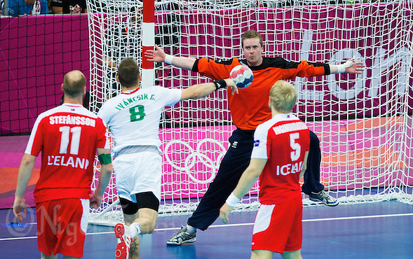 08 AUG 2012 - LONDON, GBR - Goalkeeper Hreidar Levy Gudmundsson (ISL) of Iceland (#16, in dark blue and orange) tries to  save a shot from Gergö Ivancsik (HUN) of Hungary (second from left)  during their men's London 2012 Olympic Games quarter final match at the Basketball Arena in the Olympic Park, in Stratford, London, Great Britain (PHOTO (C) 2012 NIGEL FARROW) (NIGEL FARROW/(C) 2012 NIGEL FARROW)