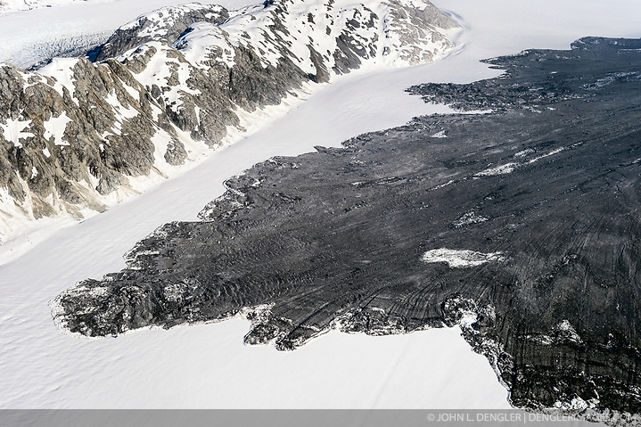 "A 4,000-foot-high mountainside released approximately 120 million metric tons of rock in 60 seconds during a landslide onto the Lamplugh Glacier in Glacier Bay National Park and Preserve. In an interview with the Alaska Dispatch News, geophysicist Colin Stark of Columbia University's Lamont-Doherty Earth Observatory, described the slide as ""exceptionally large."" He compared the massive landslide to roughly 60 million medium SUVs tumbling down a mountainside. The slide occurred on the morning of June 28 in a remote area of Glacier Bay National Park in southeast Alaska. It was first observed by Paul Swanstrom, pilot and owner of Haines-based Mountain Flying Service. Swanstrom noticed a huge cloud of dust over the Lamplugh Glacier during a flightseeing tour of Glacier Bay National Park several hours after the slide occurred. Swanstrom estimates the debris field to be 6.5 miles long, and one to two miles in width. This aerial photo of the Lamplugh Glacier landslide was taken two days after the landslide. (© John L. Dengler/Dengler Images)"
