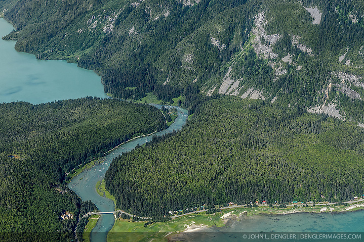 The Chilkoot River corridor between Chilkoot Lake (upper left) and Lutak Inlet of the Lynn Canal (bottom right) is a popular sport fishing spot and a culturally important Tlingit historic site. The river area is also popular with grizzly bears who also come for the salmon who spawn in the Chilkoot River. While this concentration of bears makes for exciting bear viewing for visitors, the narrow corridor in which humans and bears must pass can lead to dangerous encounters. The Alaska Legislature has approved $1 million for a bear-viewing platform aimed at reducing encounters between bears and visitors to the scenic corridor. This area is part of the popular Chilkoot Lake State Recreation Site. In the upper reaches of the Chilkoot River Valley (not pictured) there have been proposals to dam the outlet of Connelly Lake, a high alpine lake above the Chilkoot River, for a hydroelectric project. Environmental concerns include the impact construction and project operation would have on fish spawning and rearing habitat (water turbidity issues), and bald eagles. Alaska Power and Telephone announced in June 2013 that it was putting the project on hold citing difficulty securing funding from the Alaska Energy Authority and the lack of community support. Despite these setbacks AP&T says that it not abandoning pursuing the project. In early September 2013, the Haines Borough announced that it was exploring possibly filing for a preliminary permit now that the project was no longer being pursued by AP&T. (John L. Dengler)