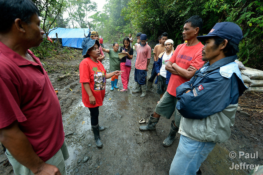 Vicklyn Ebanes (second from left), talks with other miners in the Diwalwal area on the Philippines' southern island of Mindanao. She and her husband operate a small gold mine, and she is a leader of several similar mining families who are fighting back against plans to displace them by the Philippine Mining Development Corporation, a front company for foreign mining companies that seeks to install a large-scale open pit gold mine in the area, also known as Mt. Diwata. The small miners were given notice to evacuate the area by June 5 or risk being forcibly removed by the military. The miners have defiantly refused to leave, and formed a formal association to demand respect for their rights in the Philippines courts. Ebanes, 44, is the chairperson of the local Catholic parish council, and was chosen as the association's secretary..