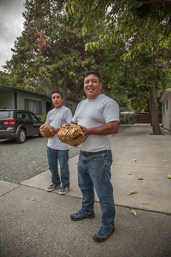 "Manuel Rodriguez and his 13 yeare old son, Adan, play catch in the driveway just minutes before the start of Game One of the World Series. ""We are rooting for Kansas City...this is their year...they deserve it."" rodriguez.adan29@yahoo.com (© Clark James Mishler)"