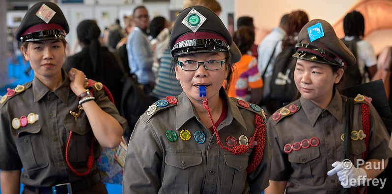 "At the 2018 International AIDS Conference in Amsterdam, a group of Taiwanese sex workers, dressed as police officers, patrols the Global Village asking people if they have a condom. If they do, they place them temporarily ""under arrest."" (If they don't have a condom they'll give you one from a big bag marked ""evidence."") The women say that Taiwan's police will use such a thin pretext as possession of a condom to charge women with a crime. It's typical, they say, of the criminalization of sex work around the world, something that's complicating the struggle against HIV and AIDS. (Paul Jeffrey)"
