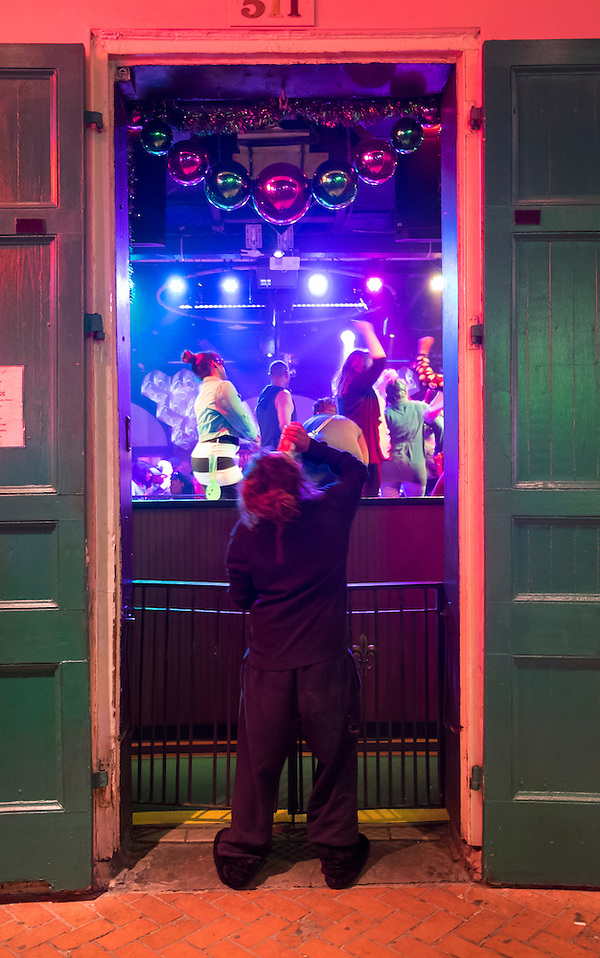 NEW ORLEANS - CIRCA FEBRUARY 2014: Woman drinking a beer in front of a nightclub during Mardi Gras celebrations in the French Quarter in New Orleans (Daniel Korzeniewski)