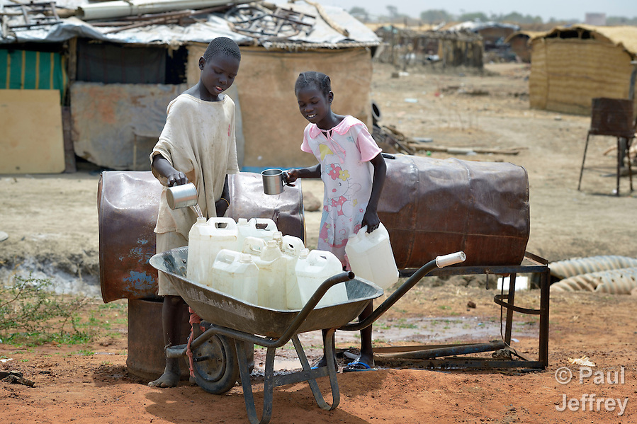 A boy and girl collect water in Abyei, a town at the center of the contested Abyei region along the border between Sudan and South Sudan. Homes here were looted and burned in 2011 when soldiers and militias from the northern Republic of Sudan swept through the area, chasing out more than 100,000 Dinka Ngok residents. A few thousand families have returned since northern combatants withdrew in 2012, yet their life is precarious. Although United Nations peacekeepers from Ethiopia today patrol the region, renewed attacks by northern-backed Misseriya militias in 2013 have many worried. The African Union has proposed a new peace plan, including a referendum to be held in October 2013, but it has been rejected by the Misseriya and Khartoum. The UN mission here also provides water to these roadside containers from which residents can obtain safe drinking water. The town's wells were destroyed by the northern combatants before they left in 2012. (Paul Jeffrey)