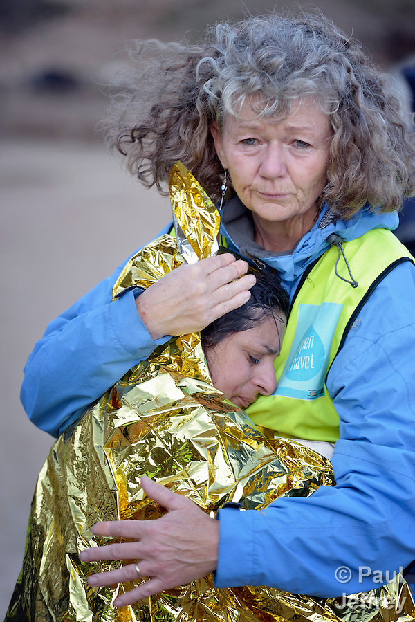 Lisbeth Sagen Lundin, a volunteer from Norway, hugs a frightened Syrian refugee on a beach near Molyvos, on the Greek island of Lesbos, on October 30, 2015. The woman was on a boat full of refugees that traveled to Lesbos from Turkey. The boat was provided by Turkish traffickers to whom the refugees paid huge sums to arrive in Greece. Lundin is one of hundreds of volunteers on the island who receive the refugees and provide them with warm clothing and medical care before they continue their journey toward western Europe. (Paul Jeffrey)