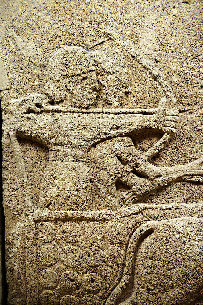 Picture & image of a Neo-Hittite orthostat with a chariot Releif sculpture from Karkamis,, Turkey. Ancora Archaeological Museum. The Cahiot is pulled by horses with plumed headresses. One man os about to shoot an arrow from his bow, the other man is driving the cahriot. Below the horse is a animal cowering. 6 (Paul E Williams)