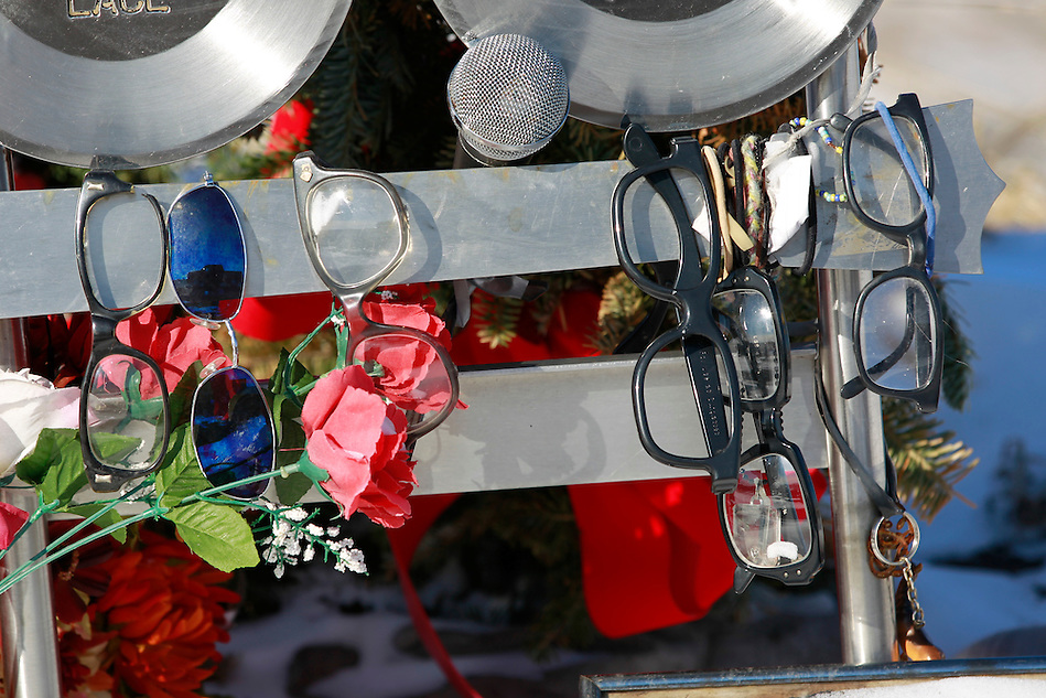 "1/19/12 3:42:10 PM -- Clear Lake, IA, U.S.A. -- THIS IS FOR A LIFE COVER:.Horn-rimmed glasses, flowers and a microphone hang from a memorial at the site of the 1959 plane crash that killed  Buddy Holly, Ritchie Valens and J.P. ""The Big Bopper"" Richardson a few miles outside of Clear Lake, Iowa..On Feb. 3, 1959, Buddy Holly, Ritchie Valens and the Big Bopper died when their plane crashed in a farm field north of Clear Lake, Iowa ? an event memorialized as ?the day the music died? in the 1971 song American Pie by Don McLean. The three 1950s stars played their last gigs at Clear Lake?s Surf Ballroom, which is intact today and holds an annual celebration of its moment in music history. The ballroom, largely the same as it was in its ?50s heyday, struggled as a for-profit business and has been operated as a non-profit since 2008. It hosts concerts, weddings, reunions and school tours. It has a small museum, but the big draw is the place itself. The maple dance floor and booths are original. One of the two original coat checks is still there and so is the phone that Holly used to call his wife before the fatal crash, the website boasts. The fun part is the annual gathering of fans from all over the world, which this year is Feb. 1-4 and is delicately called the ?winter dance party.? There are concerts each night, a bus outing to the crash site, which is marked by a giant pair of the glasses Holly wore, dance lessons, video and art contests and a gathering of the British Buddy Holly Society (whose members have been coming to Clear Lake for 23 years). Chuck Berry is a featured performer this year. It?s a charming and weird slice of Iowa life and rock ?n? roll history. -- ...Photo by Christopher Gannon for USA TODAY. (Christopher Gannon/for USA TODAY)"