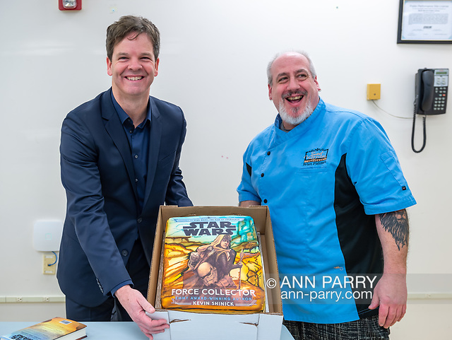 Merrick, New York, U.S. December 20, 2019. L-R, Author KEVIN SHINICK and his childhood friend BRIAN FISHMAN hold up cake Fishman decorated with cover of Shinick's book STAR WARS: FORCE COLLECTOR during book signing at North Merrick Library on Nassau County Force Collector Day.(© 2019 Ann Parry/Ann-Parry.com)