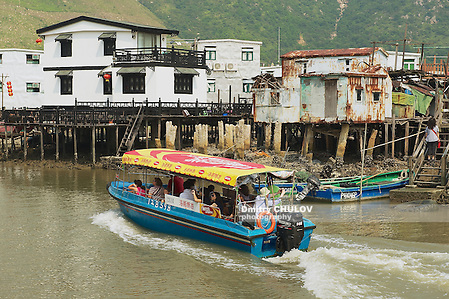 HONG KONG, CHINA - SEPTEMBER 15, 2012: Unidentified tourists enjoy boat trip at the Tai O fishermen village with stilt houses in Hong Kong, China. Tai O is a famous tourist destination in Hong Kong. (Dmitry Chulov)
