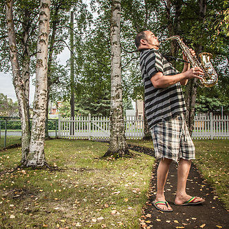 Maintenance man, musician, and neighbor, Hugo Disla, practices his saxaphone in his front yard on G Street, South Addition, Anchorage.  (Merengue/Pericoripiao music)  glorianadalexforever@hotmail.com (Clark James Mishler)