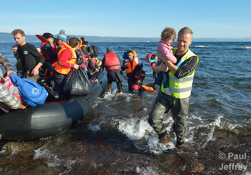 A volunteer carries ashore a small child as refugees land on a beach near Molyvos, on the Greek island of Lesbos, on November 3, 2015, after crossing the Aegean Sea from Turkey. Local and international volunteers welcomed the arriving refugees with food and medical care and dry clothes before the newcomers proceeded on their way toward western Europe. Their boat to Greece was provided by Turkish traffickers to whom the refugees paid huge sums to arrive in Greece. (Paul Jeffrey)