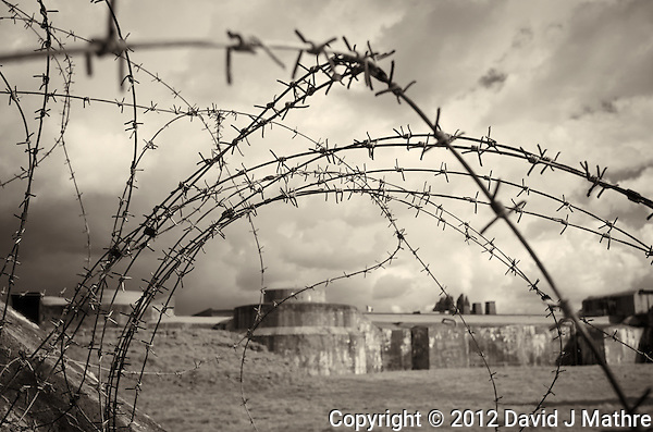 Looking Through the Barbed-Wire Fence into the WWII Prison Camp at Fort Breendonk Near Antwerp in Belgium. Image taken with a Leica X2 camera (ISO 100, 24 mm, f/6.3, 1/800 sec). Raw image processed with Capture One Pro 7 (including conversion to B&W). (David J Mathre)