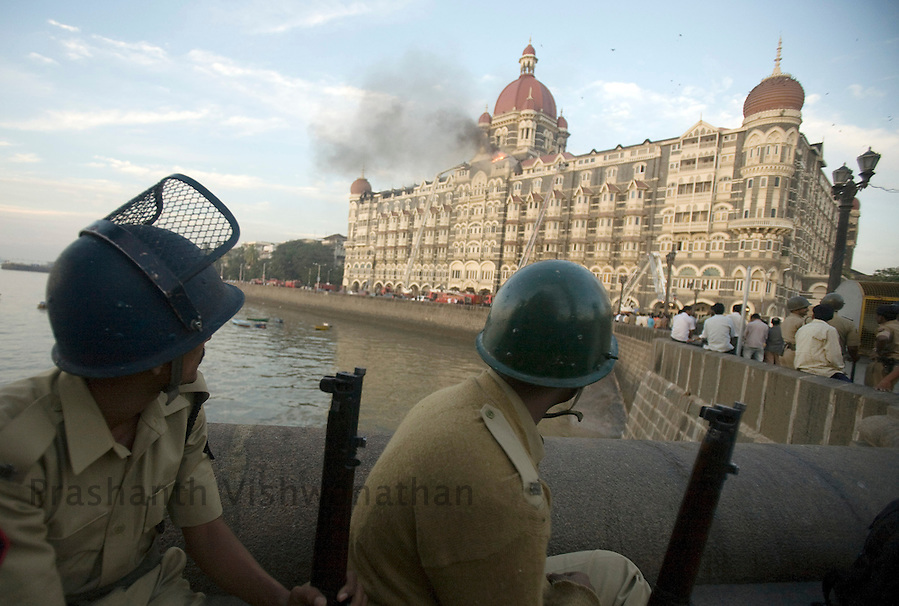 Police personell watch the taj Mahal Hotel set ablaze by terrorists in Mumbai, on Thursday, Nov. 25, 2008.  Photographer:Prashanth Vishwanathan (Prashanth Vishwanathan/BLOOMBERG NEWS)