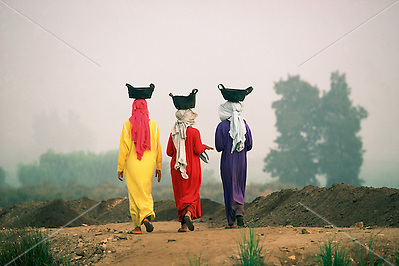 Egypt, 2000 - Three local girls in colorful dresses walk through the Mendes dig site while balancing baskets on their heads. The baskets are filled with earth from excavation at the dig site near Mansura in the Nile Delta. The bright yellow, red, and purple dresses are the girls work clothes. (Alexander Nesbitt)