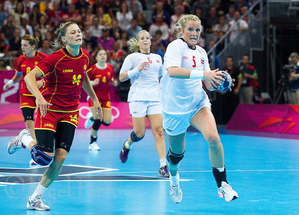 11 AUG 2012 - LONDON, GBR - Ida Alstad (NOR) (right) of Norway tries to beat Maja Savic (MNE) (left) of Montenegro up the court during the two teams women's London 2012 Olympic Games handball final at the Basketball Arena in the Olympic Park, in Stratford, London, Great Britain (PHOTO (C) 2012 NIGEL FARROW) (NIGEL FARROW/(C) 2012 NIGEL FARROW)