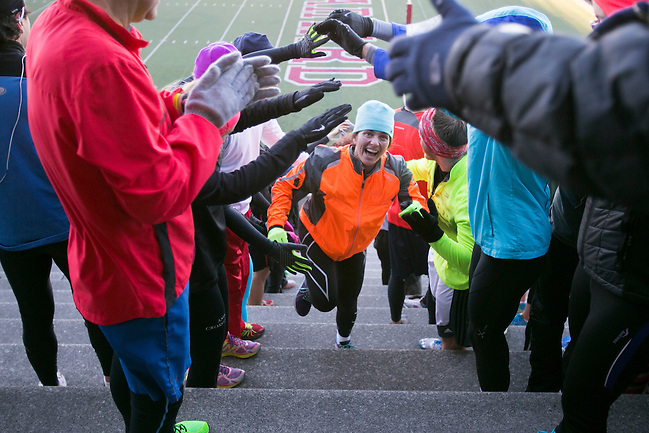11/20/2013 -- BOSTON -- November Project member Nina DeLuca, 52, is greeted with a tunnel of hands as she runs up the second to last-section of her workout at Harvard Stadium on Nov. 20, 2013.