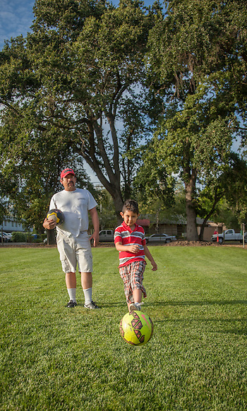 Leo Garcia gives his six year old son, Eric, a few pointers on kicking the soccer ball at Logvy filed in Calistoga (Clark James Mishler)