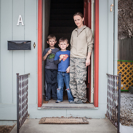 "Air Force Pharmacy Tech Marian McLaughlin and her sons at the front door of her home in Anchorage's South Addition.  ""I really don't know what I want to be…I'm fairly sure I don't want to be a pharmacist.  Right now, I love living downtown…this may be the best kept secret in town.""  mariangmclaughlin@gmail.com (© Clark James Mishler)"