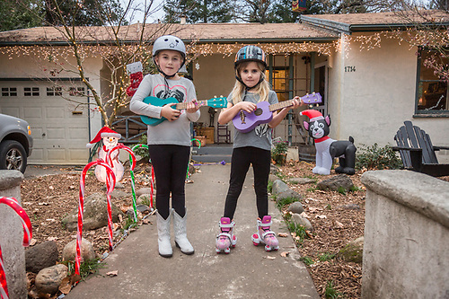 """We got these for Christmas...we're taking lessons at school.""  -Sisters Lola and Lucia practice their ukuleles in front of their  home on Cedar Street in Calistoga (Clark James Mishler)"