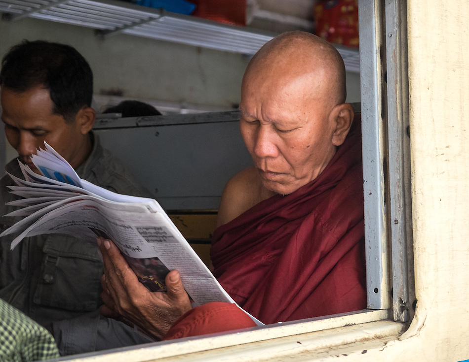 YANGON, MYANMAR - CIRCA DECEMBER 2013: Monk reading newspaper while awaits train to depart from Yangon Central Railway Station (Daniel Korzeniewski)