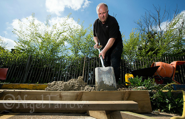 16 MAY 2015 - IPSWICH, GBR - Bryan Harvey, the Track Manager for Ipswich Cycle Speedway Club, repairing the terracing at the club's track at Whitton Sports and Community Centre in Ipswich, Suffolk, Great Britain (PHOTO COPYRIGHT © 2015 NIGEL FARROW, ALL RIGHTS RESERVED) (NIGEL FARROW/COPYRIGHT © 2015 NIGEL FARROW : www.nigelfarrow.com)