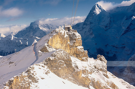 Birg station before Schilthorn. Schilthorn is a 2,970 metre high summit in the Bernese Alps in Switzerland, above Mürren. It has a panorama, which spans from the Titlis, Jungfrau, Mönch, Eiger, over the Bernese Alps and the Jura mountains up to the Vosges Mountains and the Black Forest. Mont Blanc is also just visible. A series of four cable cars, known as the Luftseilbahn Stechelberg-Mürren-Schilthorn (LSMS), provides transportation from Mürren downhill to Gimmelwald and Stechelberg, and uphill to the summit of the Schilthorn and the revolving restaurant Piz Gloria. This was a principal filming location for the James Bond movie On Her Majesty's Secret Service, released in 1969. To get to the Schilthorn from the valley floor either of a series of cable cars must be taken. The cable cars begin in Stechelberg leaving to Gimmelwald and then onto Mürren. From Mürren another cable car is taken to Birg, which is the final change before the Schilthorn. The other way up is to take the cable car from Lauterbrunnen to Grütschalp and a train to Muerren, from where the cable car must be taken. Between Birg and the summit, the cable car passes over Grauseeli, a small lake. It is also possible to hike to the peak, along the myriad of small, but well-marked paths to the top. The hike to the top takes roughly 5 hours from Gimmelwald for an experienced hiker. There is a panoramic revolving restaurant, named Piz Gloria, at the summit, which is where the James Bond movie On Her Majesty's Secret Service was set. A famous black ski run featured in the film starts at the summit and leads down to the Engetal below Birg. The restaurant revolves a full 360 degrees in 55 minutes. (Dmitry Chulov)