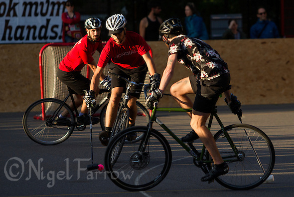 17 AUG 2014 - LONDON, GBR - A player from Mondial (in red and black) tries to find a way past a Triple Jay opponent (in black) during the 2014 London Open bike polo tournament final in Highbury Fields in London, Great Britain (PHOTO COPYRIGHT © 2014 NIGEL FARROW, ALL RIGHTS RESERVED) (NIGEL FARROW/COPYRIGHT © 2014 NIGEL FARROW : www.nigelfarrow.com)