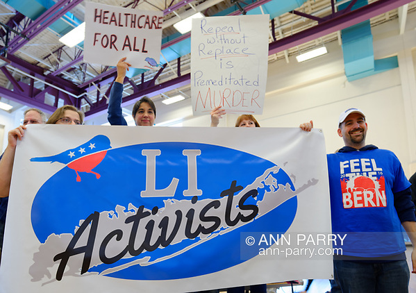 Westbury, New York, USA. Jan. 15, 2017. LI Activists group members bring a large banner and signs, and one wears