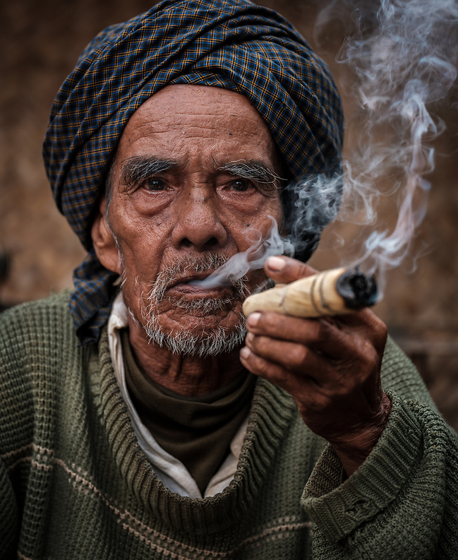BAGAN, MYANMAR - CIRCA DECEMBER 2017: Old man from a village around Bagan moking. (Daniel Korzeniewski)
