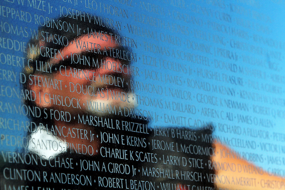 Vietnam-era veteran Kevin Baker of Des Moines looks at panels bearing the names of those killed or missing in the Vietnam War during assembly of The Dignity Memorial Vietnam Experience Wednesday at Resthaven Cemetery in West Des Moines.  The display, a traveling, three-quarter-scale replica of the Vietnam Veterans Memorial in Washington, D.C., will be open to school children on Thursday and to the public at  from Friday to Sunday. The faux-granite replica is 240 feet long, eight feet high and contains the names of more than 58,000 Americans who died or are missing in Vietnam. More than 30,000 people are expected to see the display while it is in West Des Moines.  (Christopher Gannon/The Des Moines Register) (Christopher Gannon/The Register)