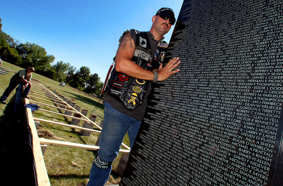 Vietnam-era veteran Jeff Kerr of Ankeny  holds a panel bearing the names of those killed or missing in the Vietnam War during assembly of The Dignity Memorial Vietnam Experience Wednesday at Resthaven Cemetery in West Des Moines.  The display, a traveling, three-quarter-scale replica of the Vietnam Veterans Memorial in Washington, D.C., will be open to school children on Thursday and to the public at  from Friday to Sunday. The faux-granite replica is 240 feet long, eight feet high and contains the names of more than 58,000 Americans who died or are missing in Vietnam. More than 30,000 people are expected to see the display while it is in West Des Moines.  (Christopher Gannon/The Des Moines Register) (Christopher Gannon/The Register)