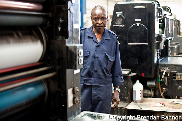 Phares Okoth, operator of Coulorprint's Offset-letterset printer. The machine has made nearly 200 million page prints in its more than 40 years of service. (Photographer: Brendan Bannon)