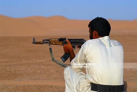 HADRAMAUT VALLEY, YEMEN - SEPTEMBER 11, 2006: Unidentified Yemeni man aim with kalashnikov machine gun in the desert, Hadramaut valley, Yemen. (Dmitry Chulov)