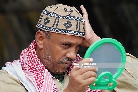 Man trying traditional yemeni headwear at the souk of Sana'a city. (Dmitry Chulov)