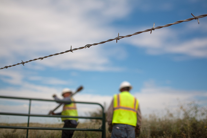 A construction crew works on a fence along the new highway under construction near The Waste Isolation Pilot Plant in Eddy County. WIPP received $172 million as part of the Recovery and Reinvestment Act. The highway will increase access for trucks carrying nuclear waste to the WIPP. (Steven St. John)