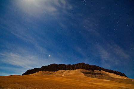 A full moon just out of the frame casts a swath of light onto Crown Butte, Montana, near Simms. (Benjamin Chase)