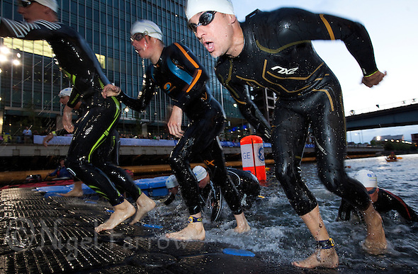 30 JUN 2011 - LONDON, GBR - Competitors leave the water at the end of the swim during the men's supersprint final at the GE Canary Wharf Triathlon (PHOTO (C) NIGEL FARROW) (NIGEL FARROW/(C) 2011 NIGEL FARROW)