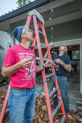"""We just realized that we've put thise up backward...we need to turn them arround so we can plug them in."" -Michael Bode with assistance from his son, Steven, reattaches a string of lights to the gutters of his home on Cedar Street in Calistoga (Clark James Mishler)"