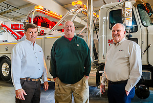 Mike Adams (centered) stands beside Tommy Bush, left, account manager at Nextran Truck Centers, and David Bennett, right, general manager at Nextran, March 22, 2016, at Mike Adams Towing and Air Cushion Recovery in Macon, Georgia. Adams purchased most of his fleet from Nextran, including his most recent acquisition, a 2016 Mack Granite with a 50-ton Century rotator. (Photo by Carmen K. Sisson/Cloudybright) (Carmen K. Sisson/Cloudybright)