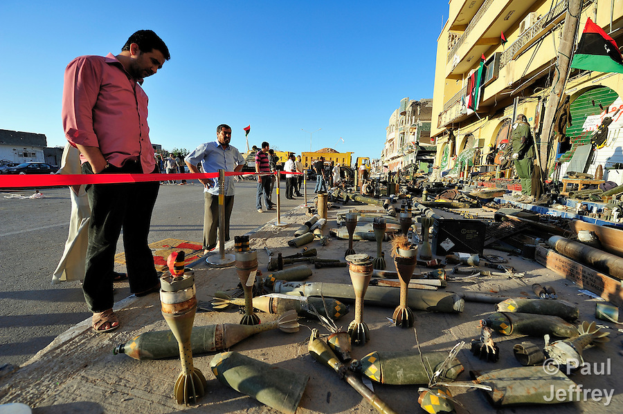 Months of fighting in Misrata, Libya, have left an abundance of ordnance scattered all over the city, some of which has been gathered by residents and placed in informal displays in front of buildings and in public spaces such as parks. Yet these informal museums include some extremely dangerous unexploded ordnance, and an ordnance disposal team from the ACT Alliance is working with local residents and city officials to neutralize the threat posed to civilians by the war debris. Here people ponder items collected in front of a building along Misrata's war-ravaged Tripoli Street..
