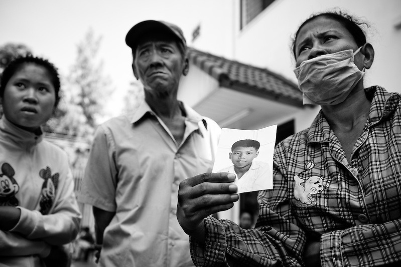 A husband and wife show the photo of their still missing fourteen year old son at Calmette Hospital in Phnom Penh, Cambodia. A young man was still unidentified here, but it wasn't their son. (Quinn Ryan Mattingly)