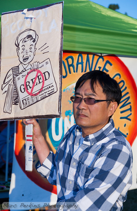 "A man walks in front of the bright orange ""Occupy Orange County - in unity with Occupy Wall Street"" banner while holding a sign with a newspaper boy holding a paper with a graphical ""No greed"" written on it. (Marc C. Perkins)"