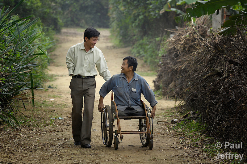 Tran Van Son (right) is a carpenter in Bo Trach, Vietnam, who lost his legs to a landmine from the U.S. war against Vietnam. Here he travels along a path near his home with Hoang Van Luu, who lost an arm to a landmine. (Paul Jeffrey)